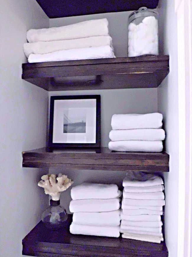 wood bathroom shelves with white towels on them