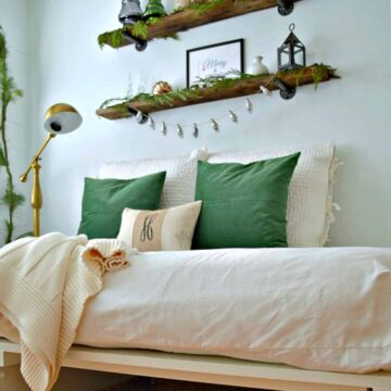 bedroom decorated for Christmas with dark green pillows