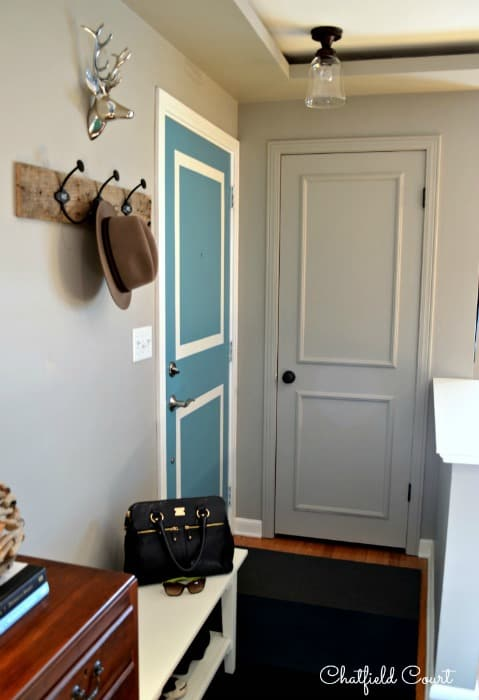 gray painted coat closet door in a small entryway