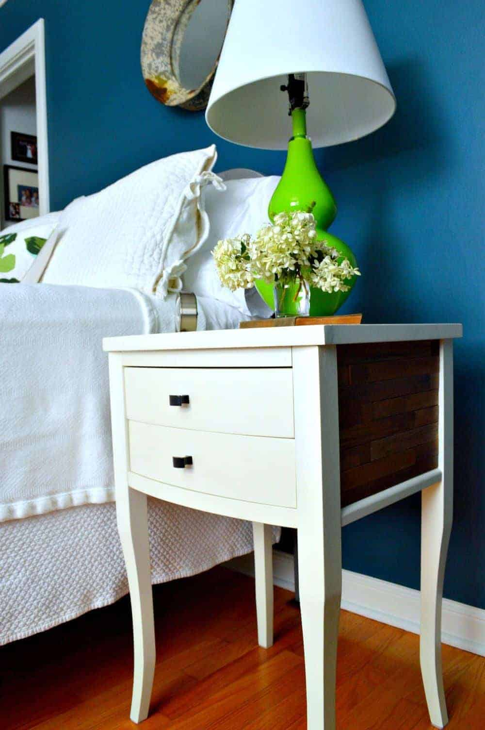 A DIY nightstand with stained wood sticks on the side next to a bed
