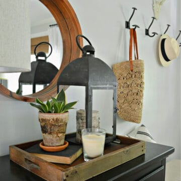 tray with lantern and potted plant on entryway cabinet