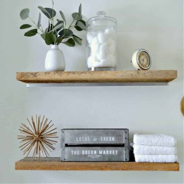 wood shelves in small bathroom with towels and cotton balls on it