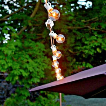 string lights hanging on a deck next to a patio umbrella