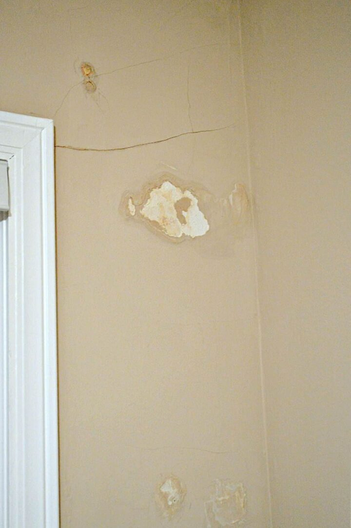 cracks and water damage on plaster wall by window