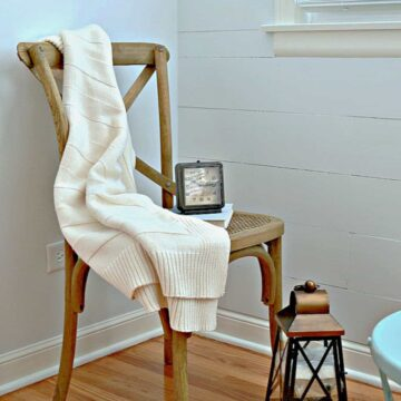 chair with throw on it in front of DIY shiplap wall