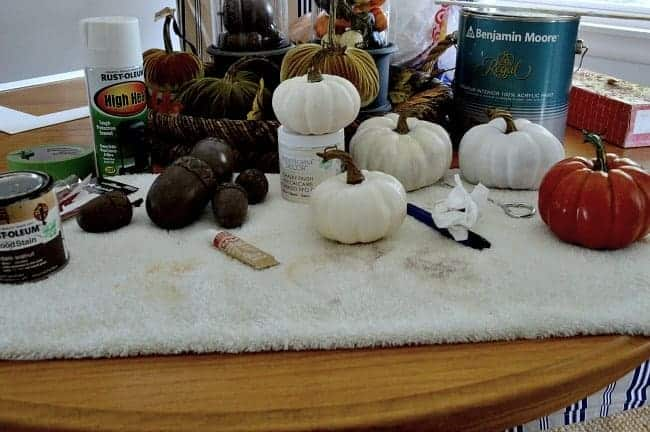 paint supplies and mini faux pumpkins on towel on dining table
