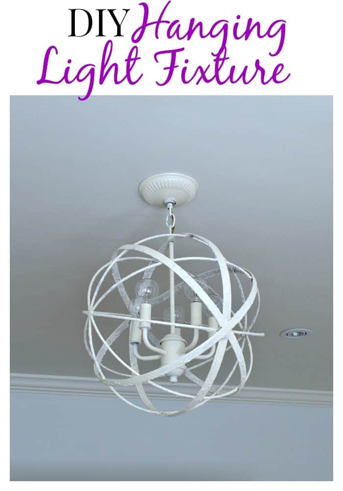 A painted DIY light fixture hanging in a bedroom