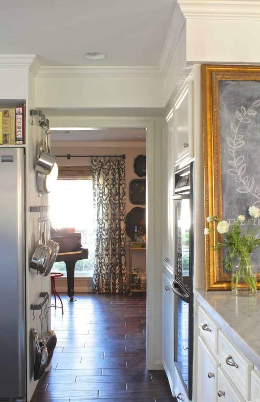 small kitchen pot storage on wall next to refrigerator