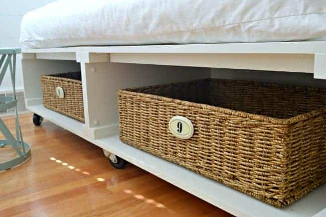 A DIY platform bed frame with numbered baskets