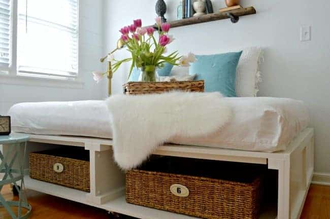 A DIY platform bed with 2 numbered baskets and faux sheepskin hanging off side