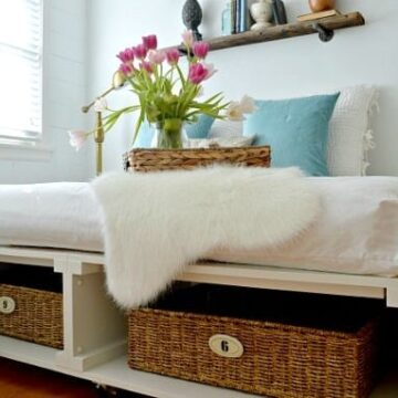 diy white painted platform bed with numbered baskets for storage