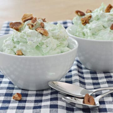 green stuff in small white bowl with nuts on top