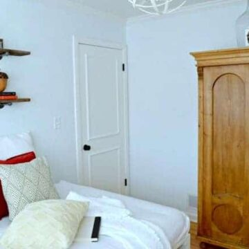 A bedroom with a bed and an armoire