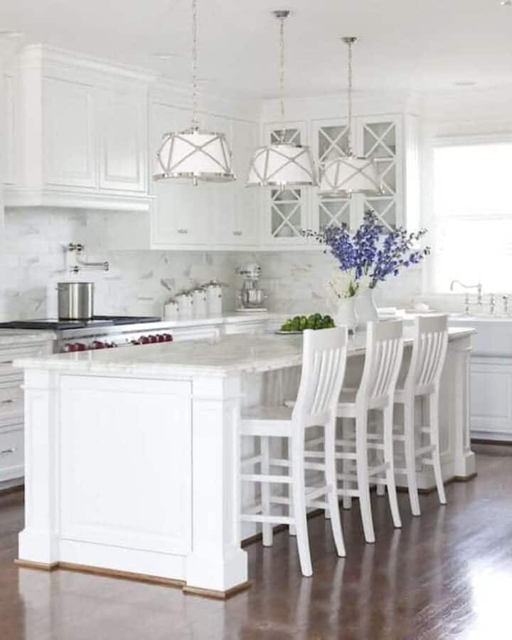 large white painted kitchen island with white chairs