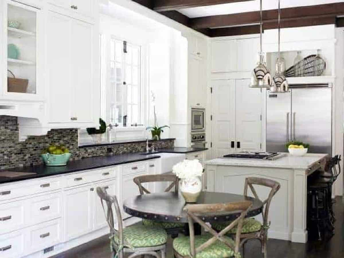 white kitchen with round wood table in the center