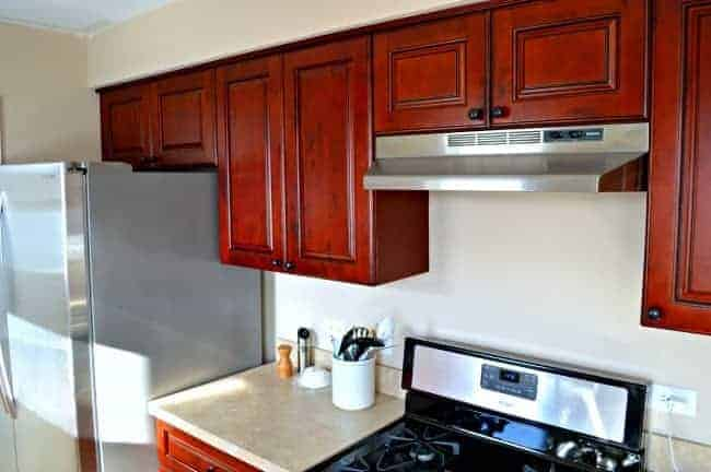 stove side of galley kitchen with red wood cabinets and stainless steel refrigerator
