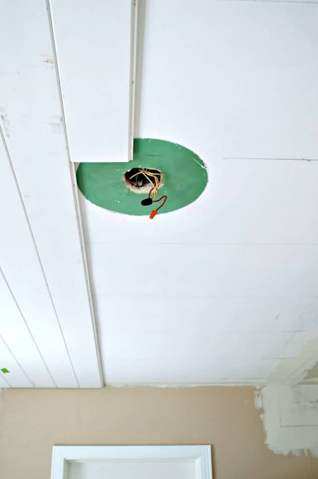 tongue and groove planks getting installed around light fixture wiring
