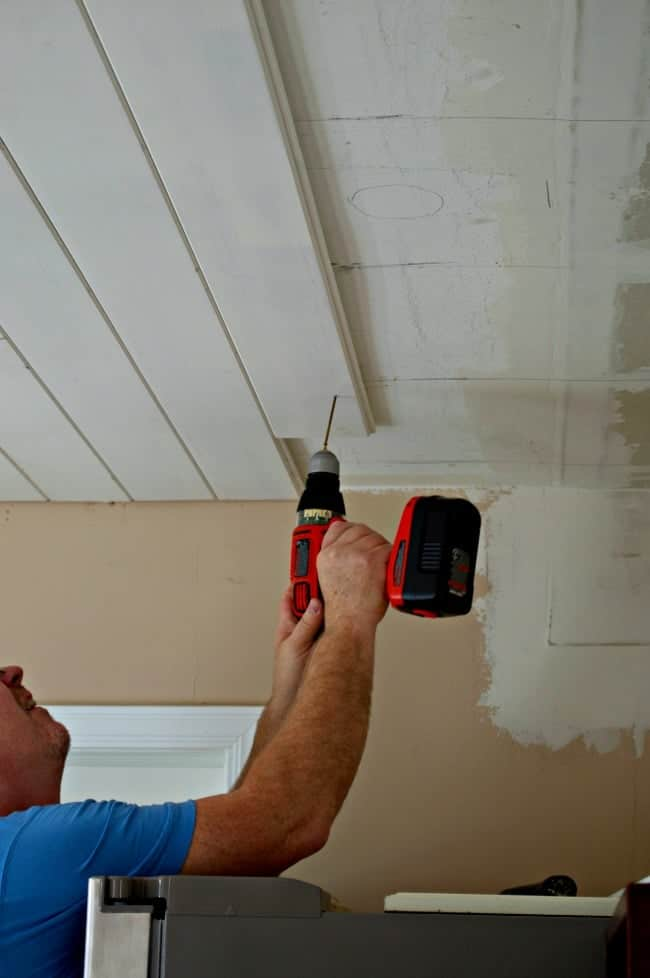 man installing screws in primed tongue and groove ceiling planks in kitchen