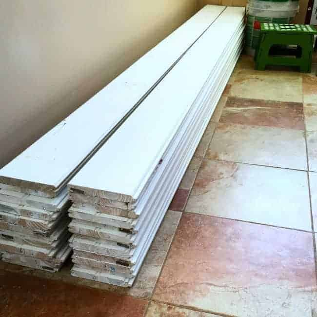 two stacks of tongue and groove planks on tiled kitchen floor