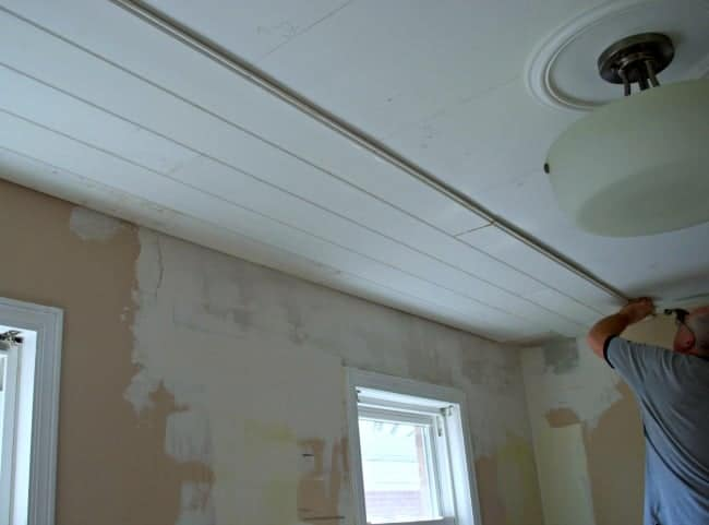 man installing primed tongue and groove ceiling planks in kitchen