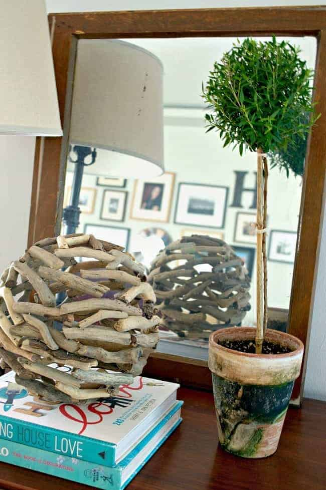 old window turned mirror with a topiary and books on a cabinet