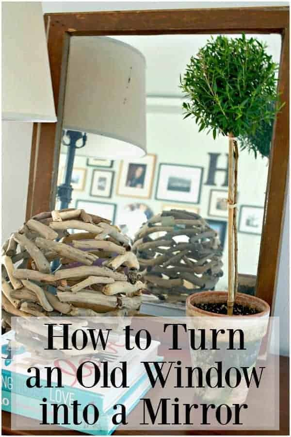 old window turned mirror on a cabinet with potted topiary and stacked books