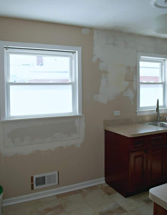 empty kitchen wall with spackle and paint swatches
