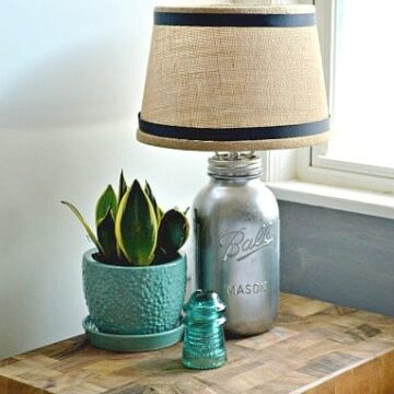 DIY mason jar lamp on wood cutting board with potted plant