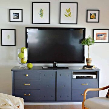 gallery wall hung around a flatscreen tv sitting on a navy cabinet