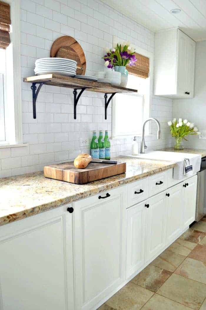white kitchen cabinets with granite countertops and subway tile backsplash