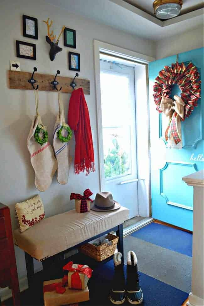 DIY ribbon wreath hanging on turquoise front door in small entryway