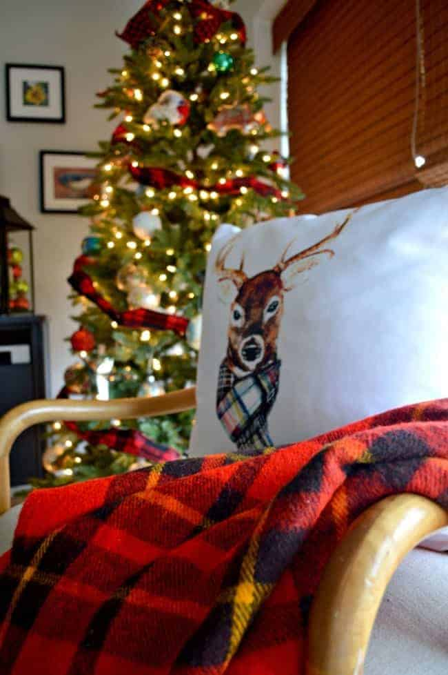 A Christmas living room decorated with lots of plaid, red and a reindeer pillow. | chatfieldcourt.com