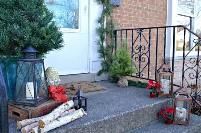 Christmas on our small front porch, which is decorated with greens, birch logs and a live mini Christmas tree | www.chatfieldcourt.com