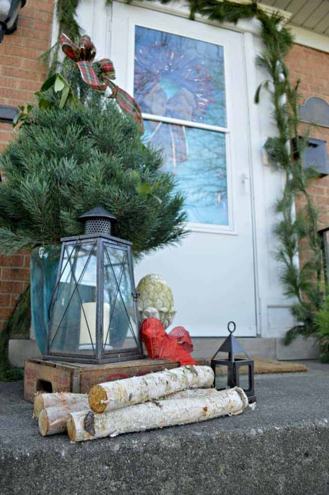 Christmas on our small front porch, which is decorated with a live mini Christmas tree, birch logs and greens | www.chatfieldcourt.com