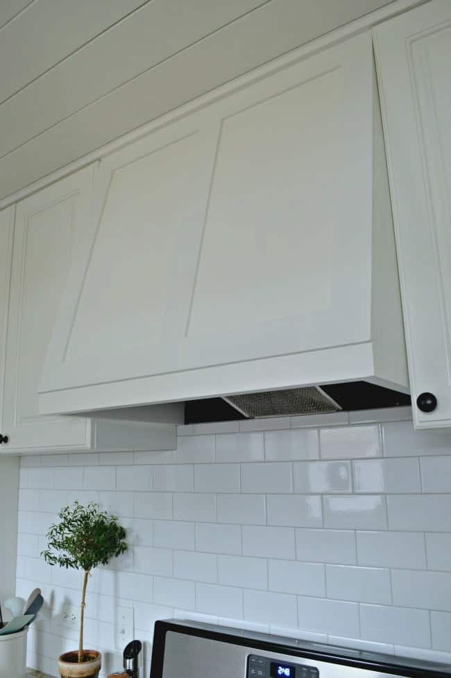 white subway tile backsplash and white kitchen stove hood