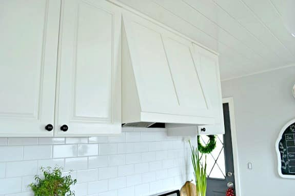 white painted cabinets and custom range hood