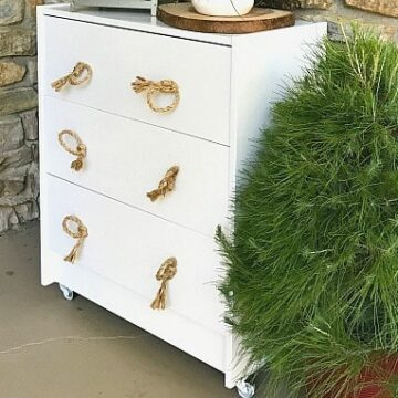 IKEA rast on front porch with rope handles and potted evergreen next to it