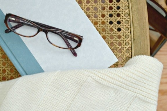 glasses on book with cozy cream throw