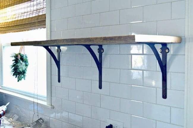How to install a rustic barn wood shelf on a tiled backsplash to add extra storage in a small kitchen. | www.chatfieldcourt.com