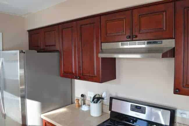 view of cherry upper kitchen cabinets and stainless steel refrigerator