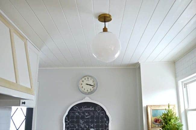 kitchen ceiling pendant and chalkboard with a clock over it