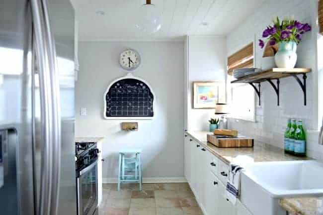 small white galley kitchen with view of chalkboard on wall and kitchen clock