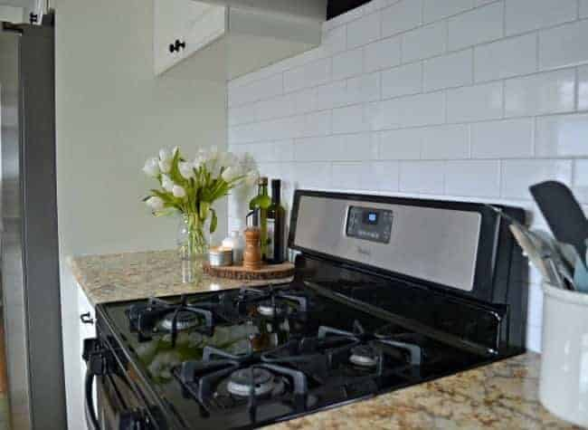stainless steel stove in white kitchen with subway tile backsplash