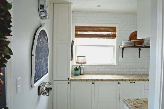 view of white kitchen cabinets and DIY chalkboard