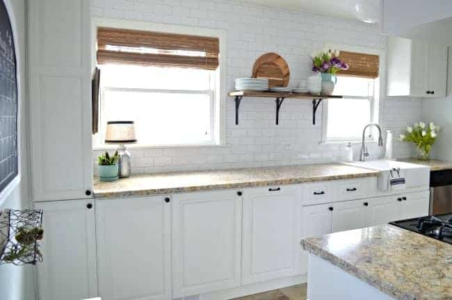 view of white painted kitchen cabinets and granite countertop with 2 kitchen windows with woven shades