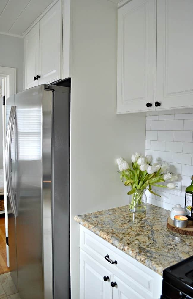 white kitchen cabinet surround around large stainless steel refrigerator