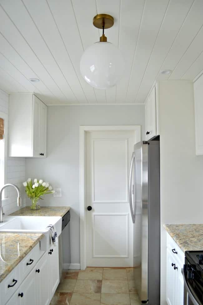 view of white galley kitchen with tongue and groove ceiling, pendant light and gray painted wall