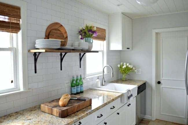 barn wood shelf and white kitchen cabinets with granite countertop