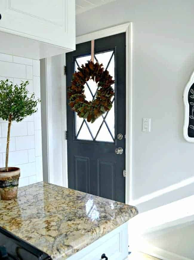 dark gray painted kitchen back door with magnolia wreath hanging on it