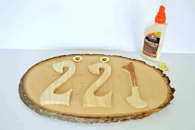 Stained wooden numbers are glued onto a wood round to create DIY rustic house numbers. | chatfieldcourt.com
